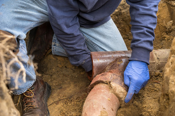 Man Digging Out Clogged Sewer Line Closeup