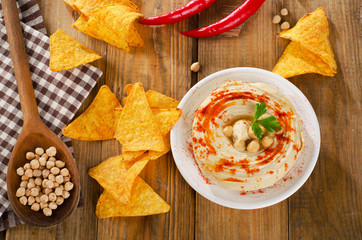 Hummus with nachos on a rustic wooden table.