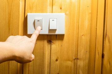 Finger press on light switch button at wooden wall.