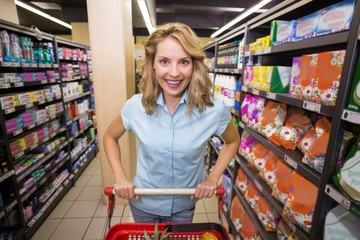 Portrait of a smiling blonde woman in aisle with her trolley