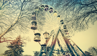 Retro old film faded picture of ferris wheel in a park.