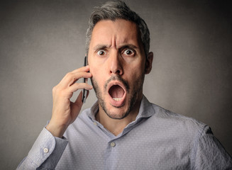 Surprised businessman doing a phone call