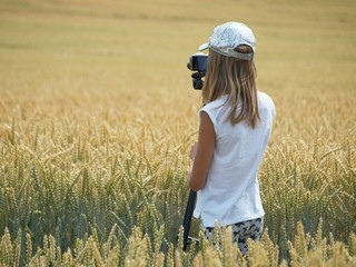 Teenage girl photographer in field of ripened wheat