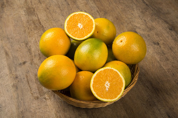 Close up of some oranges in a basket over a wooden surface
