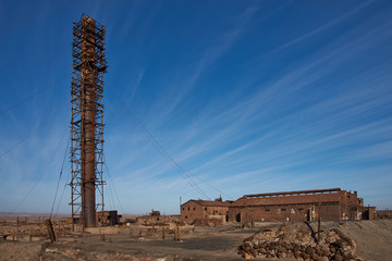 Derelict and rusting industrial buildings at the historic Humberstone Saltpeter Works in the Atacama Desert near Iquique in Chile. The site is now an open air museum and a Unesco World Heritage SIte.