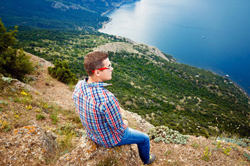 tourist sits on top of the mountain and enjoy the view of the se