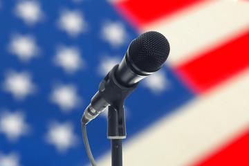 Microphone on stand with US flag on background - studio shot
