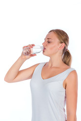 Portrait of a young happy girl drinking water from bottle after fitness, isolated on a white background