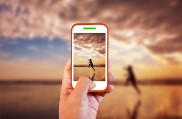 Mobile photography man running on a sandy beach.