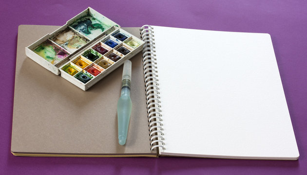 Sketchbook with blank white page, with water brush and box of watercolours