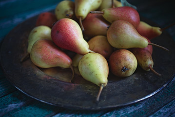 Ripe red and yellow pears, copper tray on an old wooden table
