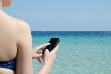 Girl send mail and sms in the beach in summer under the sun