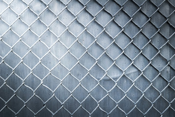steel wire mesh fence wall background with light from corner