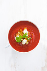 fresh gazpacho with croutons in a bowl, top view, vertical