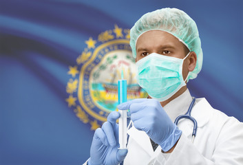 Doctor with syringe in hands and US states flags on background series - New Hampshire