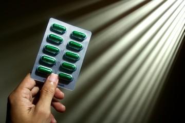 Hand holding medicine capsules