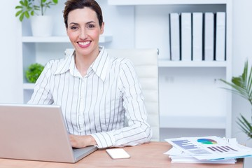 Pretty brunette smiling businesswoman using laptop