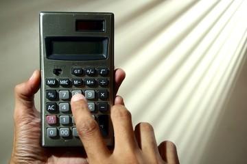 Hand holding a calculator