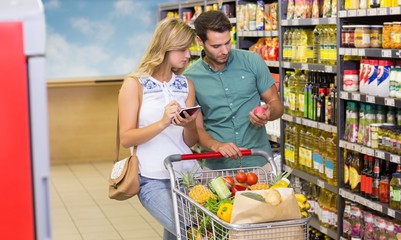 Bright couple buying food porducts and using notebook