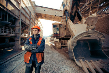 Worker man in helmet near excavator on mine career.