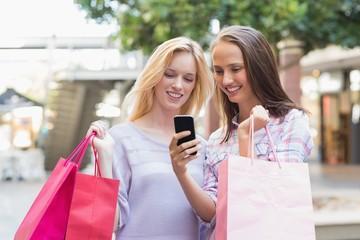 Happy women friends looking at smartphone