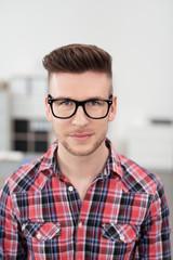 junger mann mit schwarzer brille im büro