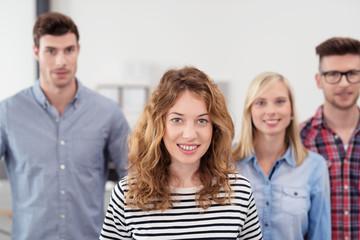 junges team im büro schaut lächelnd in die kamera