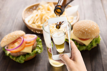 Using smartphones to take photos beer being poured into glass