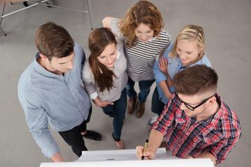 gruppe schaut auf flipchart und sammelt ideen