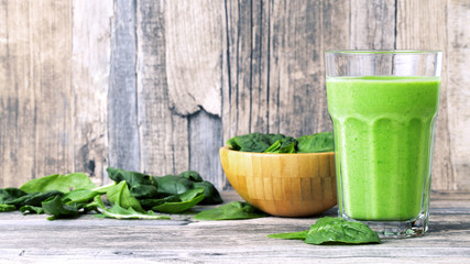 green smoothie juice on wooden table with spinach