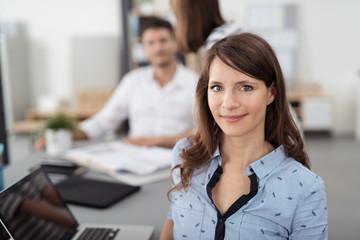 lächelnde geschäftsfrau am arbeitsplatz mit kollegen im hintergrund