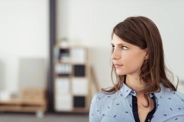 mitarbeiterin im büro schaut nachdenklich zur seite