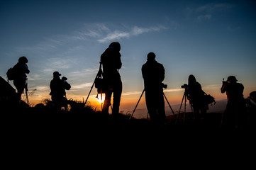 silhouette of photographer taking picture of landscape during sunrise