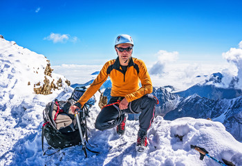 Climber on a mountain top posing on the background of snowy mountains