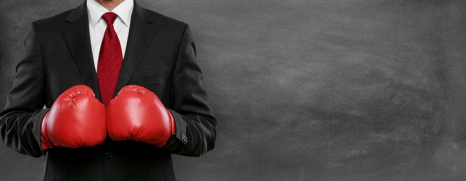 Mann im Anzug mit Boxhandschue