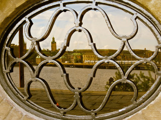 Oval window with forged lattice. Reflection of Stockholm in glass