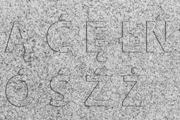 Polnische Buchstaben, polnische Sonderzeichen aus Granitstein auf einer Granitsteinplatte