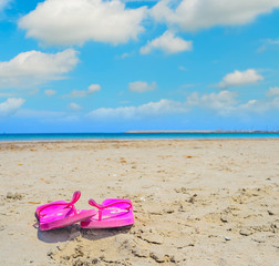 pink flip flops on the sand in Sardinia
