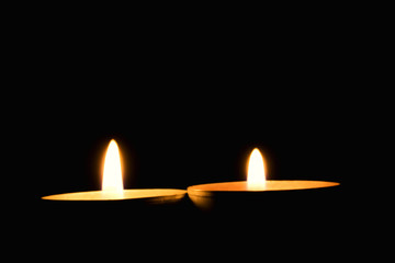 Two candles against a dark background