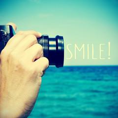 man taking a picture and the text smile!, with a retro effect