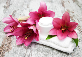 cosmetic cream and pink lily flower