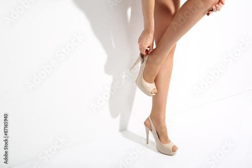 9f48ad0a58894c Kobieta zakłada buty na wysokim obcasie.Nogi kobiety w rajstopach.