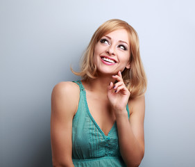 Happy toothy smiling blond woman thinking and looking up