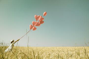 Konzept für Liebe, Freiheit, Mut. Hintergrund mit roten Luftballons und einem Mädchen im Sommer