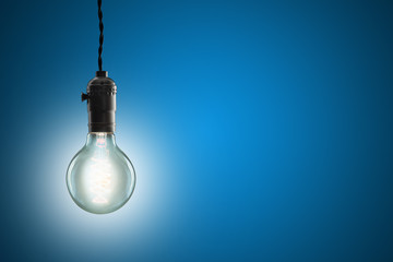 Idea concept - Vintage incandescent bulb on blue background