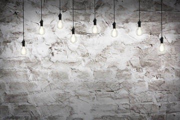 Idea concept - Vintage incandescent bulbs on wall background