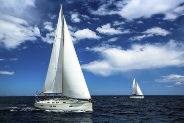 Ship yachts with white sails in the open sea. Sailing. Yachting. Luxury Lifestyle.
