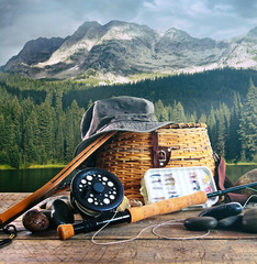 Fly fishing gear on wooden deck with lake