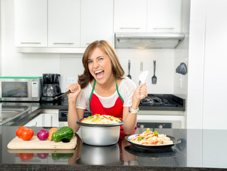 Hispanic beautiful woman cooking in modern kitchen by bench with veggies and pot of food holding a knife out sideways angry facial expression