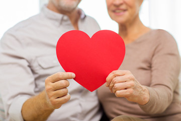 close up of happy senior couple holding red heart